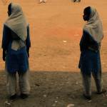 Adolescent girls play soccer on their breaks during school.