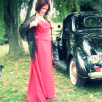 Martina models a vintage red dress in front of their vintage car. One of Marina's many dogs is included here.